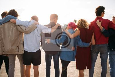 Fototapeta Tylny widok młodzi różnorodni ludzie grupy. Uzbrój się. Wsparcie dla jedności. Przyjaźń razem