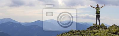 Fototapeta Tylny widok potomstw schudnięcia turysty turystyczna dziewczyna z nastroszonymi rękami stoi na skalistym wierzchołku przeciw jaskrawemu błękitnemu ranek niebu cieszy się mgłową pasmo górskie panoramę.