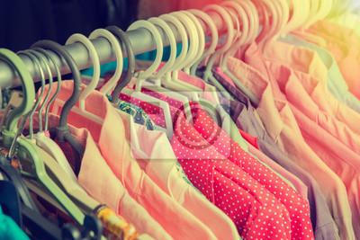 Fototapeta Ubrania wiszą na półce w sklepie w designerskich ubrań retro kol