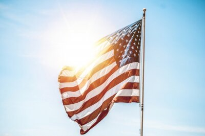 Fototapeta United States flag on the pole with the sun shining in the background