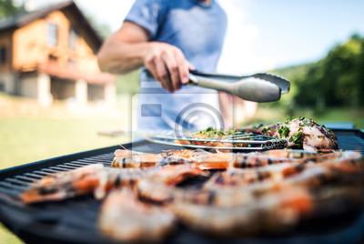 Fototapeta Unrecognizable mężczyzna kulinarny owoce morza na grilla grillu w podwórku.