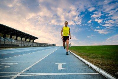 Fototapeta Uomo che Corre su pista di atletica