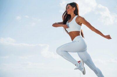 Fototapeta Up in the sky. Female runner in white sportive clothes doing fitness