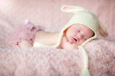 Fototapeta urocza dziewczynka urodzona w szpitalu w  gustownej czapeczce królika na różowym kocu śpi smacznie