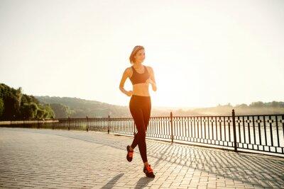 Fototapeta Uruchamianie kobietę. Jogging biegacz w jasnym świetle słonecznym. Kobieta Fitn