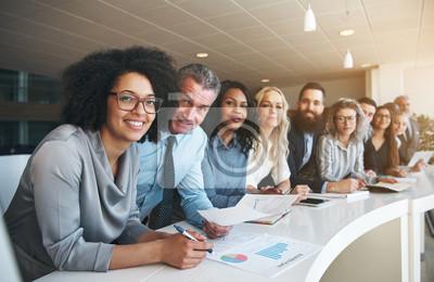 Fototapeta Uśmiechnięta grupa różnorodni koledzy pracuje wpólnie w biurze