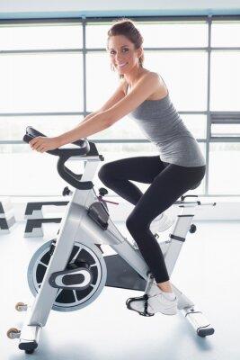 Fototapeta Uśmiechnięta kobieta szkolenia na wykonywanie rowerów