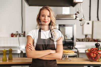 Fototapeta Uśmiechnięty młoda kobieta szefa kuchni kucharz w fartuchu
