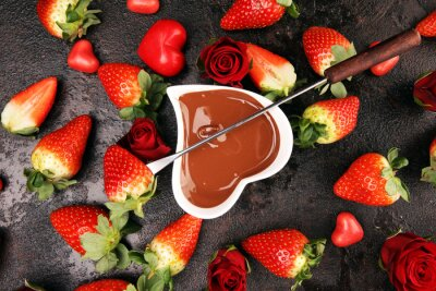 Valentine Chocolate fondue melted with fresh strawberries and dark and white chocolate. Red roses and sugar hearts for Valentines Day. Valentine Background