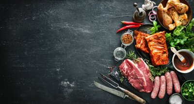 Fototapeta Various kinds of grill and bbq meats with vintage kitchen and butcher utensils