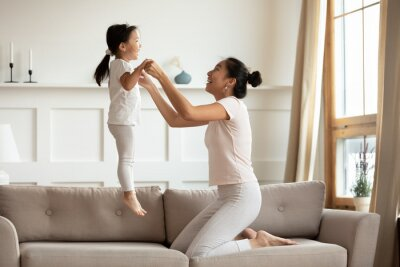 Fototapeta Vietnamese young mother holding hands of little asian toddler lively daughter while she jumping on couch in living room. Active time with children, fun and fit, playtime with child at home concept