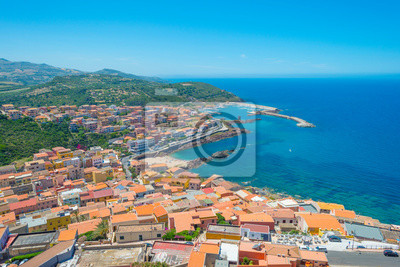 View of the town of Castelsardo on a hill and along the sea in sunlight in spring