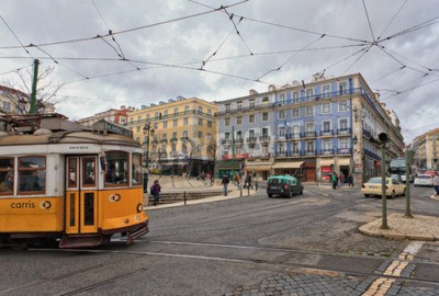 Fototapeta View of the traditional yellow Tram 28 passing through the streets of Lisbon, Portugal providing innercity public transport