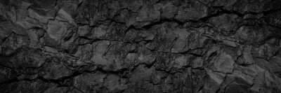 Fototapeta Volumetric rock texture with cracks. Black stone background with copy space for design. Wide banner.