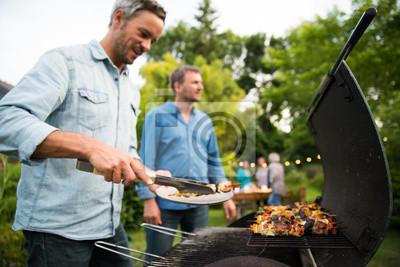 Fototapeta w letni wieczór dwóch mężczyzn po czterdziestce przygotowuje grill dla przyjaciół zebranych przy stole w ogrodzie