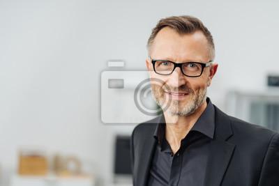 Fototapeta W średnim wieku biznesmen jest ubranym szkła
