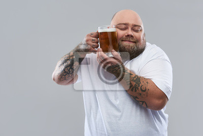 Fototapeta Waist up of bearded tattooed man pressing glass of beer to his cheek