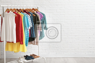 Fototapeta Wardrobe rack with stylish clothes and shoes near brick wall indoors. Space for text