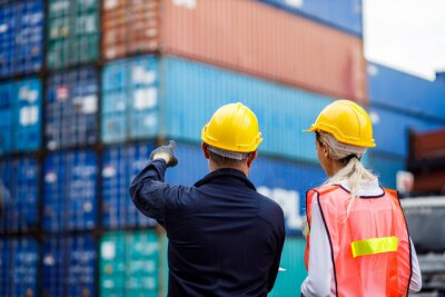 Fototapeta Warehouse shipping transportation concept. Commercial docks worker and inspector at commercial dock. Workers are wearing protective clothing they are standing against cargo containers.