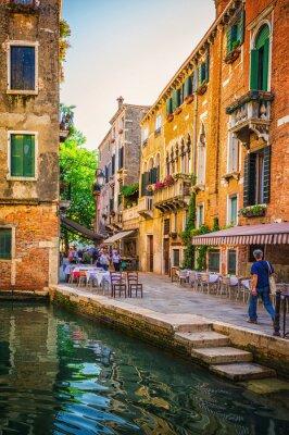Fototapeta Wąski kanał wśród starych kolorowych domów w Wenecji z cegły