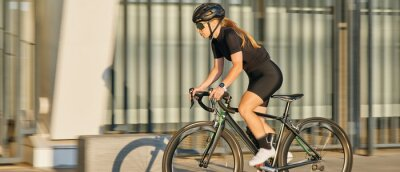 Fototapeta Website header of Side view of professional female cyclist in black cycling garment and protective gear riding bicycle in city, rushing and passing outdoors on a sunny day