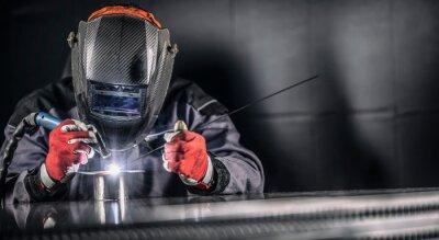Fototapeta Welder industrial worker welding with argon machine