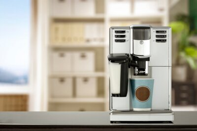White coffee machine in office and empty table of free space for your decoration.