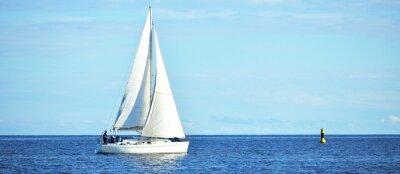 Fototapeta White sloop rigged yacht sailing near the lighthouse, close-up. Riga bay, Baltic sea. Clear blue sky. Transportation, nautical vessel, cruise, sport, regatta, recreation, leisure activity