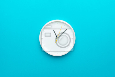 Fototapeta White wall clock with yellow second hand hanging on the wall. Minimalist flat lay image of plastic wall clock over blue turquiose background with copy space and central composition.