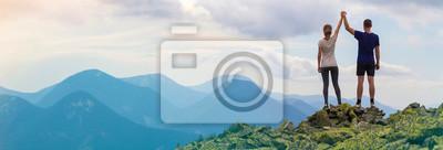 Fototapeta Widok młodej pary turystycznej, wysportowanego mężczyzny i szczupłej dziewczyny stojącej z uniesionymi rękami z tyłu, trzymając ręce na szczycie góry skalistej, ciesząc się fantastyczną panoramą. Konc