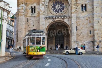Fototapeta Widok na tradycyjnych żółty tramwaj 12 przechodzącej ulicami Lizbonie zapewniając liniowa transportu publicznego