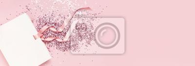 Fototapeta Widok z góry leżał płasko Biała torebka prezentowa i holograficzne konfetti z brokatem w postaci gwiazdek na różowym tle. Kartkę z życzeniami Świąteczne wakacje pastelowe tło. Gratulacje z okazji Świą