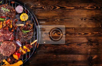 Fototapeta Widok z góry świeżego mięsa i warzyw na grilla umieszczone na drewnianych deskach