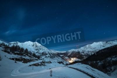 Fototapeta Widok z lotu ptaka miejscowości La Thuile świecące w nocy, znany ośrodek narciarski w Dolinie Aosty we Włoszech. wspaniałe gwiaździste niebo i majestatyczne góry oświetlone przez księżyc.