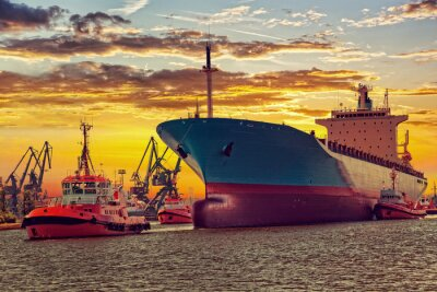 Fototapeta Wielki statek z eskortujących holowniki opuszczeniu portu na zachód słońca.