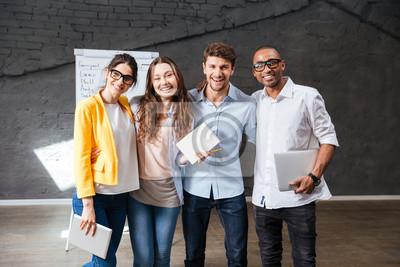 Fototapeta Wieloetniczne grupa szczęśliwych młodych ludzi stojących w biurze