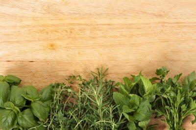 Fototapeta Wiersz świeżych ziół na starej drewnianej desce do krojenia. Przestrzeń dla współpracy