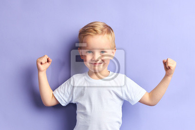 Fototapeta Winner kid isolated over purple background, show how powerful he is. Isolated over purple background