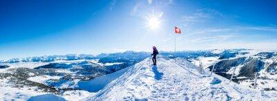 Fototapeta winter sports: snow shoe hiker a the summit of the snowy mountain in the swiss alps. panoramic switzerland mountain range
