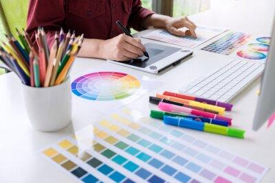 Fototapeta Wizerunek kobiet kreatywnych grafików pracujących nad wyborem kolorów i rysowaniem na tablecie graficznym w miejscu pracy