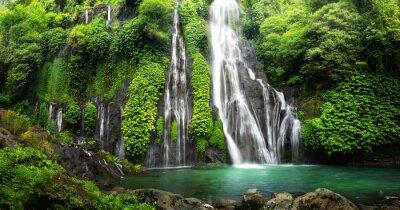 Fototapeta Wodospad kaskady dżungli w tropikalnym lesie deszczowym z rock i turkusowy niebieski staw. Ma nazwę Banyumala, ponieważ jej bliźniacze wodospady znajdują się na zboczu góry