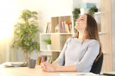 Fototapeta Woman breathing fresh air sitting on a desk at home
