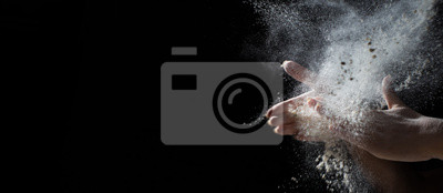 Fototapeta woman chef hand clap with splash of white flour and black background with copy space.