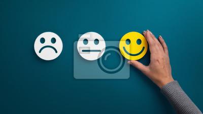 Fototapeta Woman choosing happy smiley face emotion on green