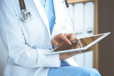 Fototapeta Woman doctor using white tablet computer while sitting at chair in hospital, close-up