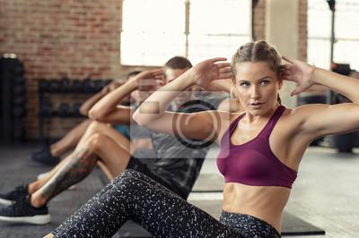 Fototapeta Woman doing abs exercise at cardio course