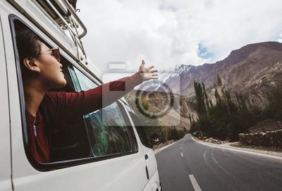 Fototapeta Woman enjoying the cool breeze from the car window