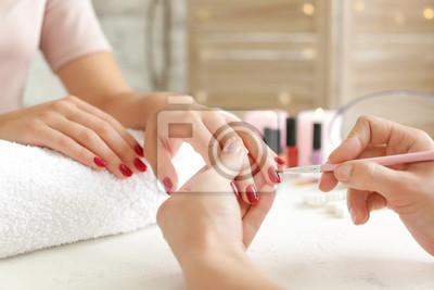 Fototapeta Woman getting professional manicure in beauty salon, closeup