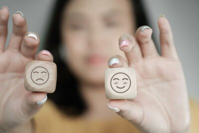 Fototapeta Woman hand holding smile and angry face on wooden cube, positive or negative thinking, mental health, Business satisfaction assessment , world mental health day concept