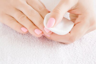 Fototapeta Woman hand removing pink nail polish with white cotton pad on white towel. Front view. Close up.
